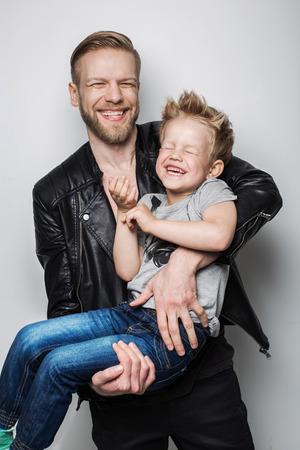 Jonge vader en zoon lachen samen. Vaderdag. Studio portret over een witte achtergrond Stockfoto