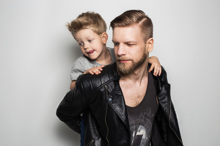 Portret van jonge aantrekkelijke lachende vader spelen met zijn kleine schattige zoon. Vaderdag. Studio portret over een witte achtergrond