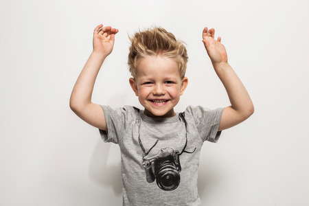 photographers: Portrait of happy joyful beautiful little boy. Studio portrait over white background
