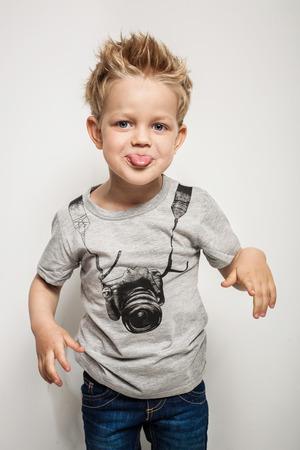 Stoute jongen een grimas en steekt zijn tong uit. Studio portret over een witte achtergrond