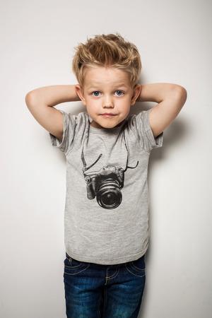 niño parado: Pequeño niño bonito que presenta en el estudio como modelo. Retrato de estudio sobre fondo blanco