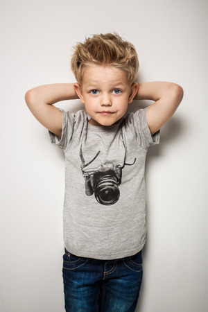 Weinig mooie jongen poseren in de studio als een mannequin. Studio portret over een witte achtergrond Stockfoto