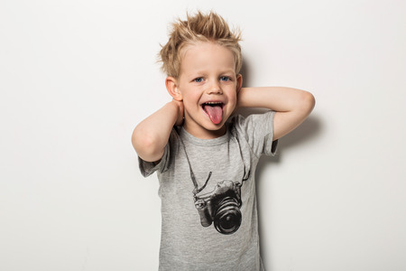 Naughty boy making a grimace and sticking his tongue out. Studio portrait over white background Standard-Bild