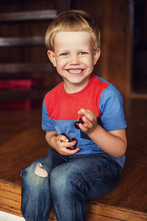 toddler boy: Happy little toddler boy eat berry. Outdoor portrait