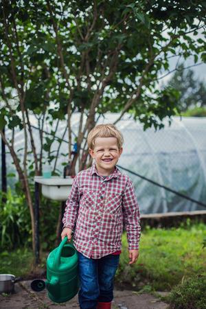 ��beautiful boy�: Beautiful boy gardening. Garden. Vegetables. Outdoors portrait Stock Photo