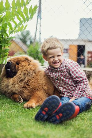 lovingly: Child lovingly embraces his pet dog. Chow Chow. Outdoor portrait