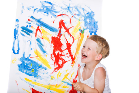 Beautiful boy painting with paintbrush on canvas. Education. Creativity. Studio portrait over white background 스톡 콘텐츠