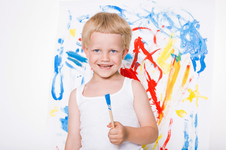 ��beautiful boy�: Little beautiful boy paints a picture. School. Preschool. Education. Creativity. Studio portrait over white background
