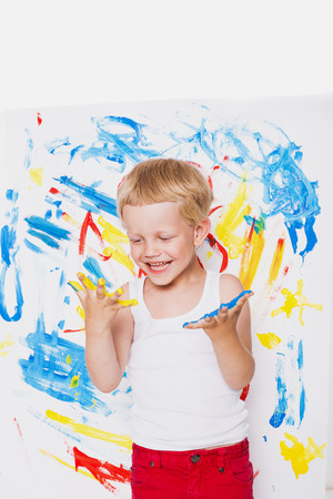 Kleine jongen trekt felle kleuren. School. Peuter. Onderwijs. Creativiteit. Studio portret op witte achtergrond
