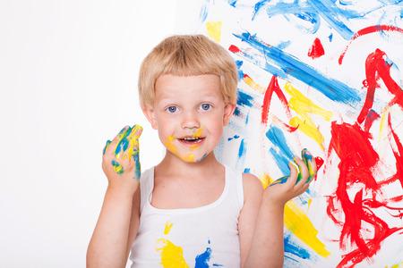 Klein kind trekt heldere kleuren. School. Peuter. Onderwijs. Creativiteit. Studio portret over een witte achtergrond