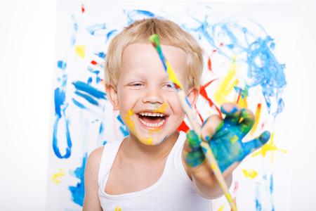 Pequeña pintura chico desordenado con la imagen brocha en caballete. Educación. Creatividad. Colegio. Preescolar. Retrato de estudio sobre fondo blanco Foto de archivo - 43807788