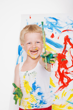 Little messy kid painting with paintbrush picture on easel. Education. Creativity. School. Preschool. Studio portrait over white background Stock Photo