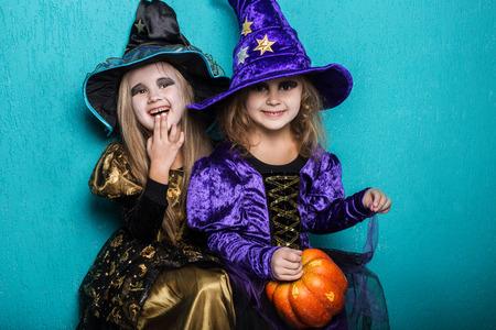 Meisjes in een kostuum van een heks. Halloween. Fee. Verhaal. Studio portret op blauwe achtergrond Stockfoto