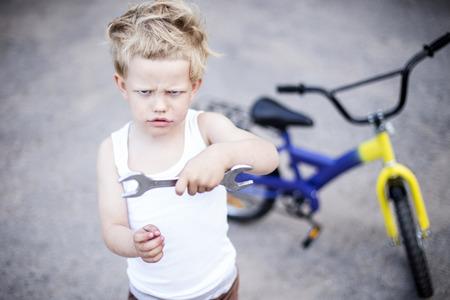 Grappige peuter jongen repareren van zijn gebroken fiets. Childhood.Cycling Stockfoto