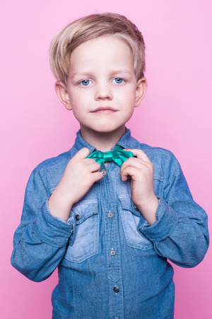 stylish boy: Young beautiful boy with blue shirt and butterfly tie. Studio portrait over pink background