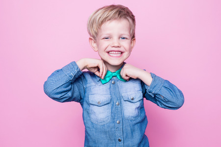 birthday boy: Young handsome kid smiling with blue shirt and butterfly tie. Studio portrait over pink background