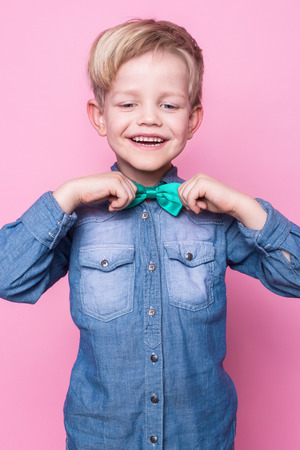 teen boy face: Young handsome kid smiling with blue shirt and butterfly tie. Studio portrait over pink background