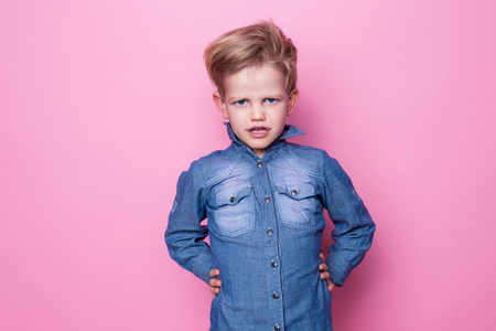 blonde boy: Portrait of angry beautiful little boy. Studio portrait over pink background
