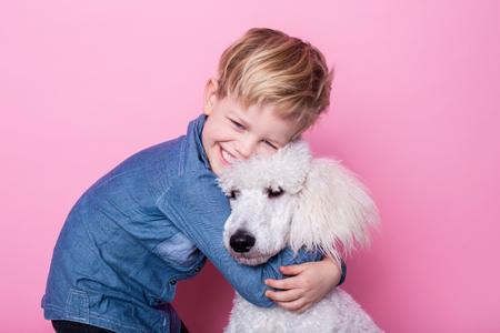 Mooie jongen met Royal Standard Poodle. Studio portret over roze achtergrond.