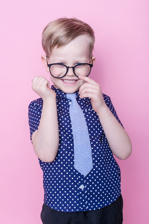 fashion boy: Portrait of a little smiling boy in a funny glasses and tie. School. Preschool. Fashion. Studio portrait over pink background Stock Photo