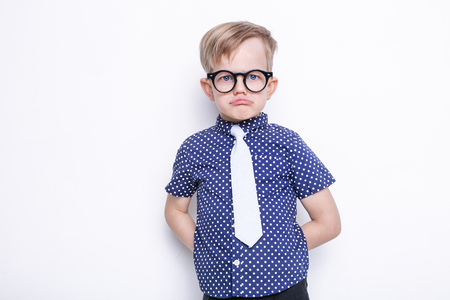 solid background: Little adorable kid in tie and glasses. School. Preschool. Fashion. Studio portrait isolated over white background