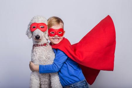 Handsome little superhero with dog. Superhero. Halloween. Studio portrait over white background