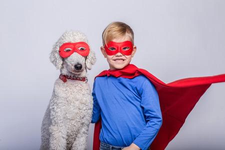 Handsome little  superhero with dog. Superhero. Halloween. Studio portrait over white background 스톡 콘텐츠