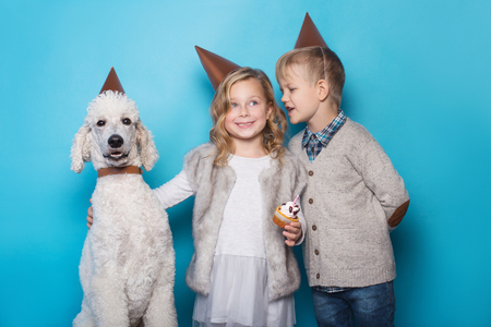 Little beautiful girl and handsome boy with dog celebrate birthday. Friendship. Family. Studio portrait over blue background Фото со стока