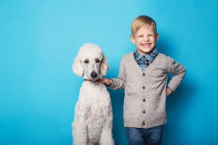 Fashionable boy with dog. Friendship. Pets. Studio portrait over blue background