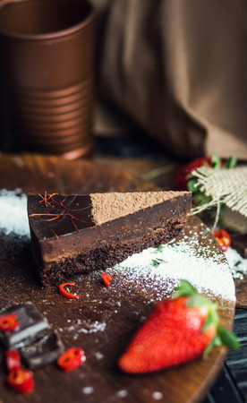 Piece of dark chocolate cake with strawberry. The restaurant or cafe atmosphere. Retro. Vintage