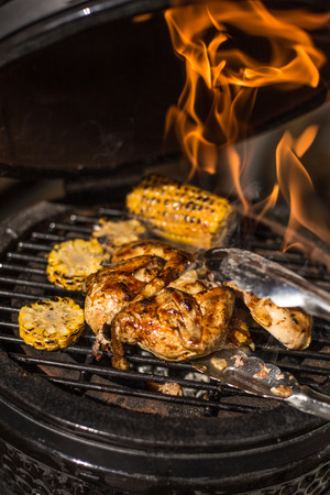 Grilled whole chicken with corn on hot flaming grill