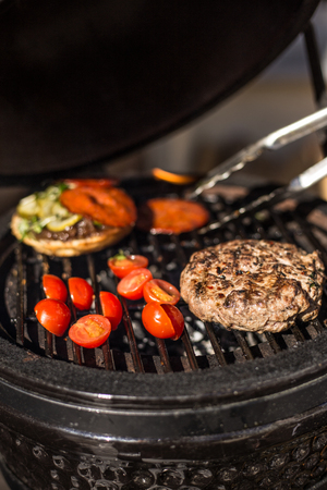 Delicious cheeseburger with tomatoes cooking on hot flaming grill