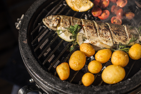 Delicious rainbow trout fish with tomatoes, potatoes and lemon cooking on hot flaming grill