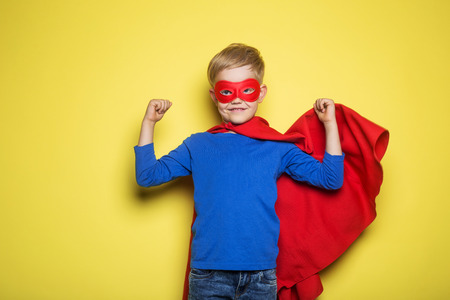 Boy in red super hero cape and mask. Superman. Studio portrait over yellow background