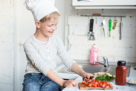 Kid chef is cooking in the kitchen at home. Healthy food