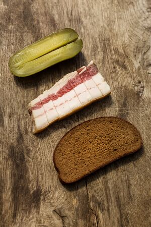 Bacon, bread and cucumber over wooden background. Russian and ukrainian traditional appetizer