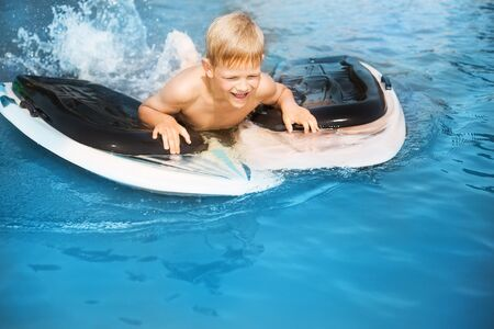 Little boy with surfboard having fun. Vacation, summer and childhood concept