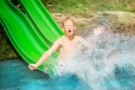 Young boy or kid has fun splashing into lake after going down water slide during summer. Vacation and childhood concept Stock Photo
