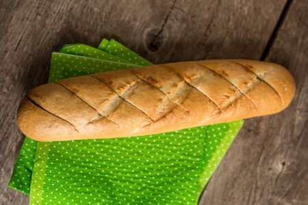 Sliced long french bread over wooden table. Baguette. Restaurant Foto de archivo - 132470310