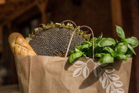 Various healthy food in paper bag on wooden background. Healthy food from the store Foto de archivo - 131818608