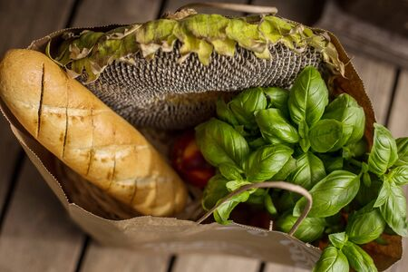 Various healthy food in paper bag on wooden background. Healthy food from the store
