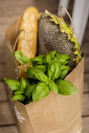 Various healthy food in paper bag on wooden background. Healthy food from the store Foto de archivo - 132470316