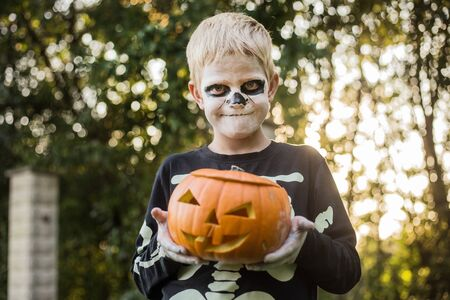 Happy young blond hair boy with skeleton costume holding jack o lantern. Halloween. Trick or treat. Outdoors portrait Foto de archivo - 131818556