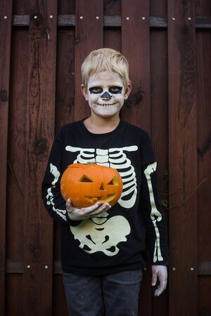 Happy young blond hair boy with skeleton costume holding jack o lantern. Halloween. Trick or treat. Outdoors portrait Foto de archivo - 131818513