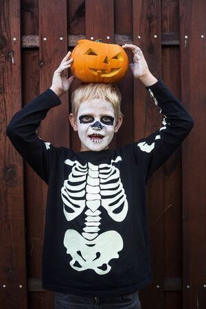 Happy young blond hair boy with skeleton costume holding jack o lantern. Halloween. Trick or treat. Outdoors portrait 版權商用圖片