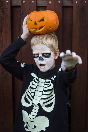 Happy young blond hair boy with skeleton costume holding jack o lantern. Halloween. Trick or treat. Outdoors portrait Stock fotó