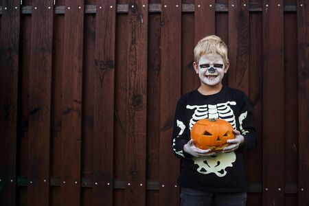 Happy young blond hair boy with skeleton costume holding jack o lantern. Halloween. Trick or treat. Outdoors portrait Foto de archivo - 131818613