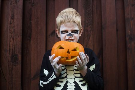 Happy young blond hair boy with skeleton costume holding jack o lantern. Halloween. Trick or treat. Outdoors portrait Stockfoto