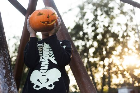 Happy young blond hair boy with skeleton costume holding jack o lantern. Halloween. Trick or treat. Outdoors portrait 스톡 콘텐츠