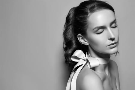 黒と白の美しい穏やかな若いブルネットの女性のファッションの肖像画を入札します。
